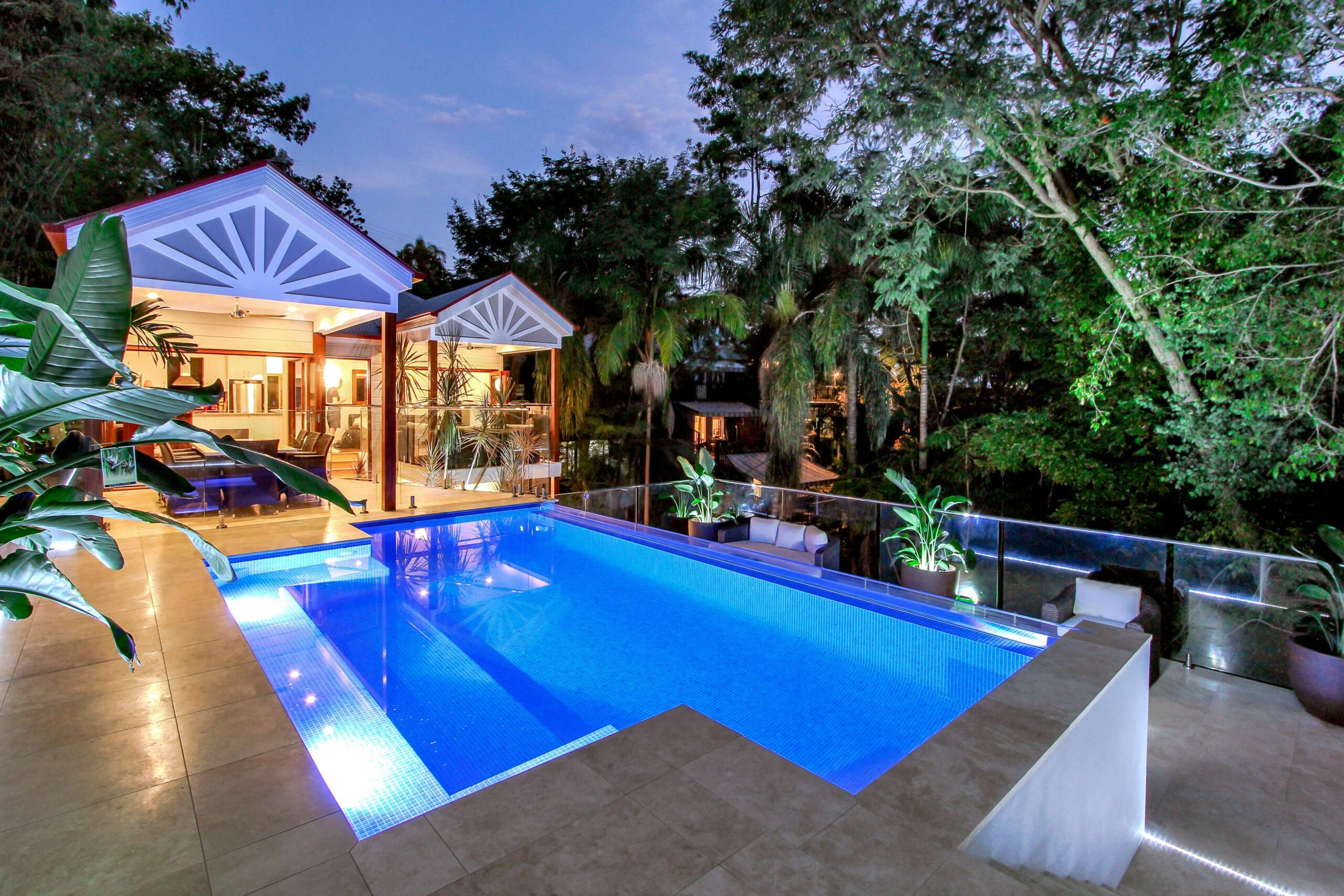 Luxury fully tiled swimming pool with lights on at night. Built you your local Gold Coast pool builders, Palm Beach Pools.